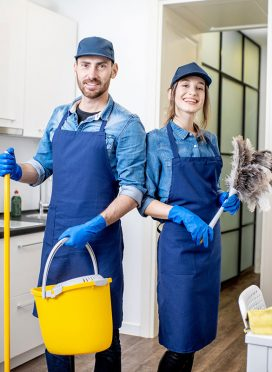 Portrait of a couple as a professional cleaners in uniform standing together with cleaning tools indoors